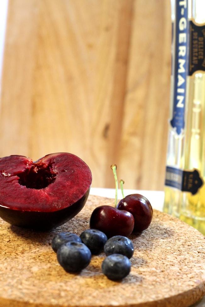 This Elderflower Sangria recipe is a delicious mix of dry white wine, elderflower liqueur, orange liqueur, blueberries, cherries, a plum and sparkling lime water.