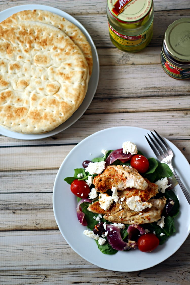 This easy baked Greek chicken with feta, lemon zest, red onion, kalamata olives and spices is a flavor-filled delight!  Place this tasty chicken on a bed of spinach with Feta cheese for a simple and delicious meal.