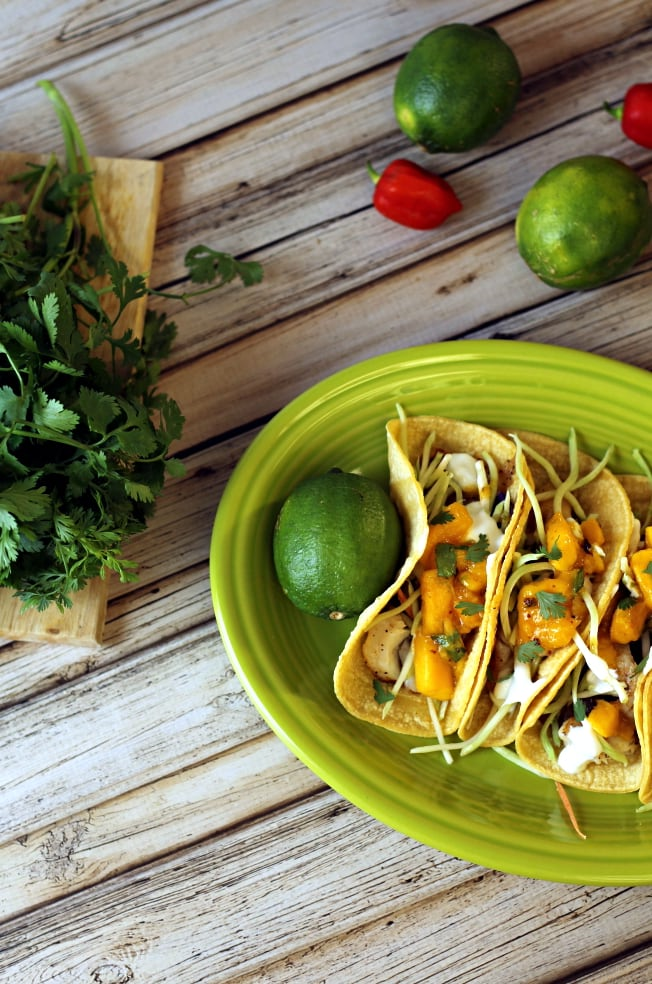 This Skinny Baja Tacos recipe is a delicious low calorie fish tacos recipe with mango salsa, seasoned white fish, broccoli slaw and Greek yogurt.