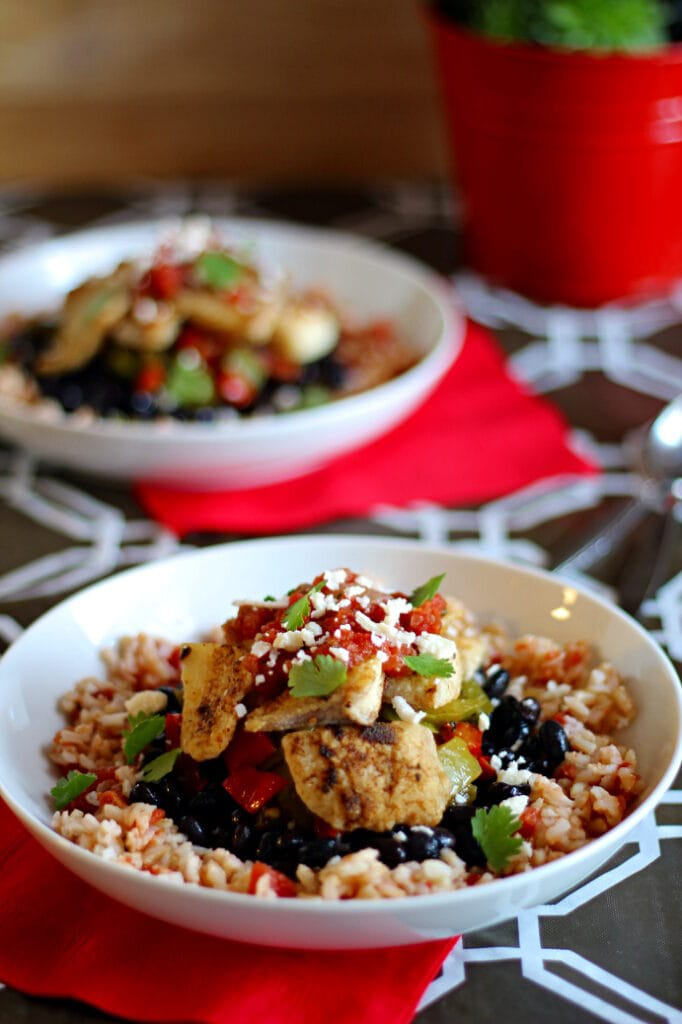This Mexican Tilapia Bowl recipe is a delicious layering of Mexican rice, black beans, fajita veggies, crispy tilapia, salsa, cotija cheese, and cilantro leaves. If you desire, go crazy and add shredded cabbage, avocado or guacamole and sour cream!