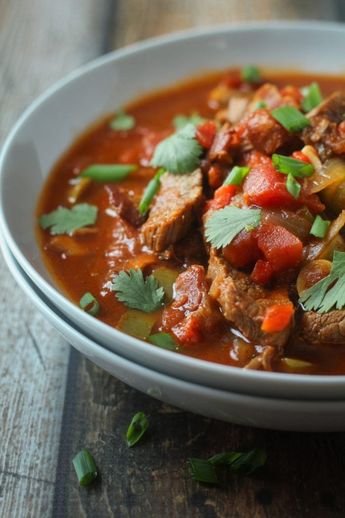 This Cuban Ropa Vieja Stew recipe makes a hearty beef Cuban stew with bacon, flank steak, red and green bell peppers, onion, tomato paste and spices that you will love!