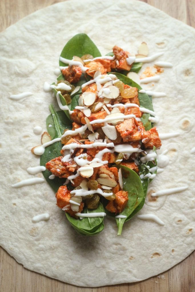 This Healthy Moroccan Chicken Wrap recipe features chicken with harissa sauce and spices, in a delicious tortilla wrap with spinach leaves, golden raisins, sliced almonds and a honey yogurt lemon sauce.