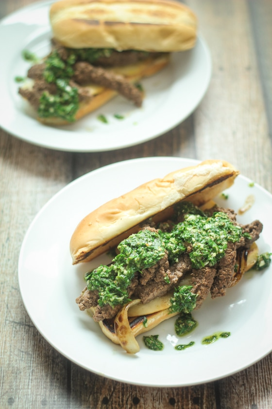 A delicious Steak Sandwich Chimichurri recipe features a hoagie roll with cheese and seasoned steak topped with sauted onions and fresh, homemade Argentinian Chimichurri Sauce.