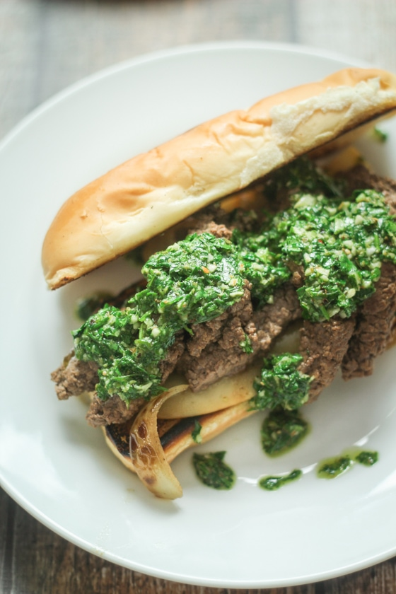 A delicious Chimichurri Steak Sandwich recipe features a hoagie roll with cheese and seasoned steak topped with sauted onions and fresh, homemade Argentinian Chimichurri Sauce.