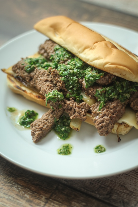 A delicious Steak Chimichurri Sandwich recipe features a hoagie roll with cheese and seasoned steak topped with sauted onions and fresh, homemade Argentinian Chimichurri Sauce.