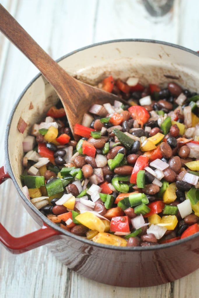 This Mexican Three Bean Salad recipe is a delicious mix of black, pinto and red beans with yellow and red bell peppers, poblano chili pepper and onion.