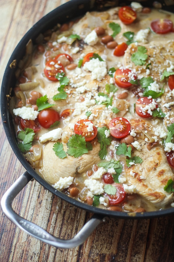 This Saucy Mexican Chicken Skillet recipe is a delicious dish of chicken, pinto beans, onion, cherry tomatoes, Cotija cheese and spices.