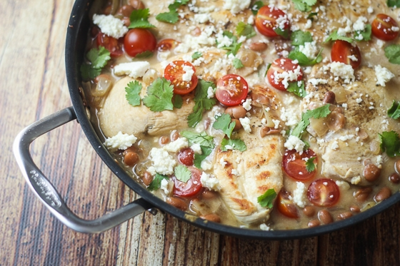 Looking for saucy chicken recipes? Try this one! This Saucy Mexican Chicken Skillet recipe is a delicious dish of chicken, pinto beans, onion, cherry tomatoes, Cotija cheese and spices.