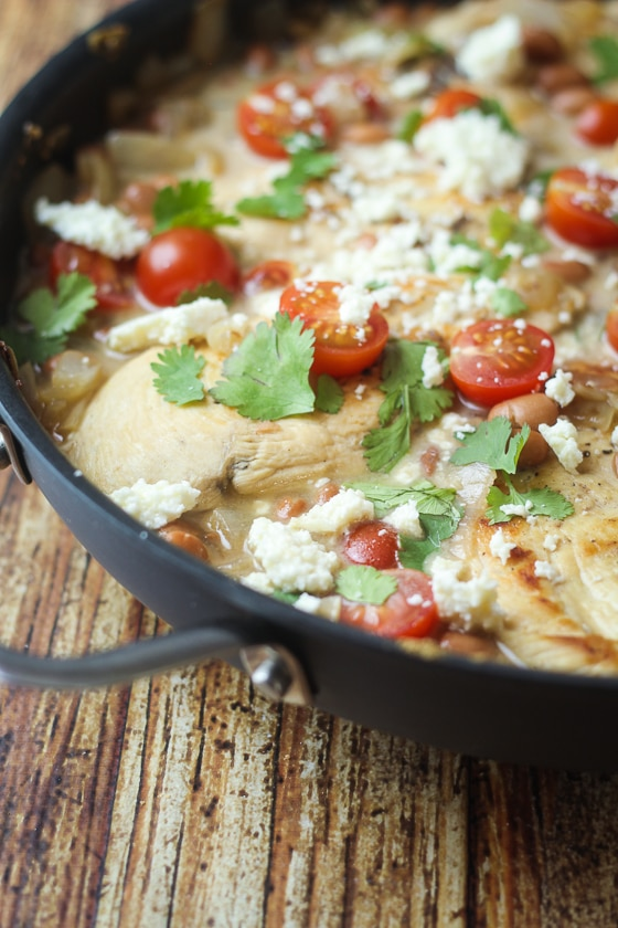 This Saucy Skillet Mexican Chicken recipe is a delicious dish of chicken, pinto beans, onion, cherry tomatoes, Cotija cheese and spices.