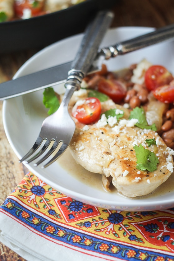 Looking for Mexican chicken recipes? Try this great one! This Saucy Mexican Chicken Skillet recipe is a delicious dish of chicken, pinto beans, onion, cherry tomatoes, Cotija cheese and spices.