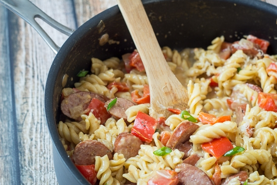 Looking for Kielbasa recipes with pasta? Try this great one! This Sausage and Peppers Pasta recipe comes together quick and easy in one pot with a delicious mix of Kielbasa, red bell pepper, yellow onion, tomatoes, Parmesan cheese and rotini pasta.