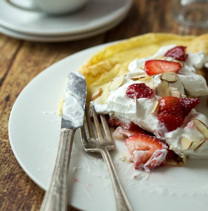 This easy, Homemade Swedish Pancakes recipe will start your day off right with these delicious pancakes topped with strawberries and whipped cream!