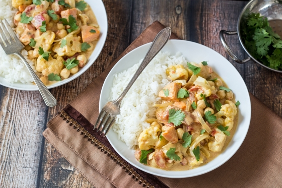 This Quick Fall Curry Vegetables recipe is a delicious mix of sweet potatoes, cauliflower, yellow onion, tomatoes, and chickpeas in a tasty curry sauce.
