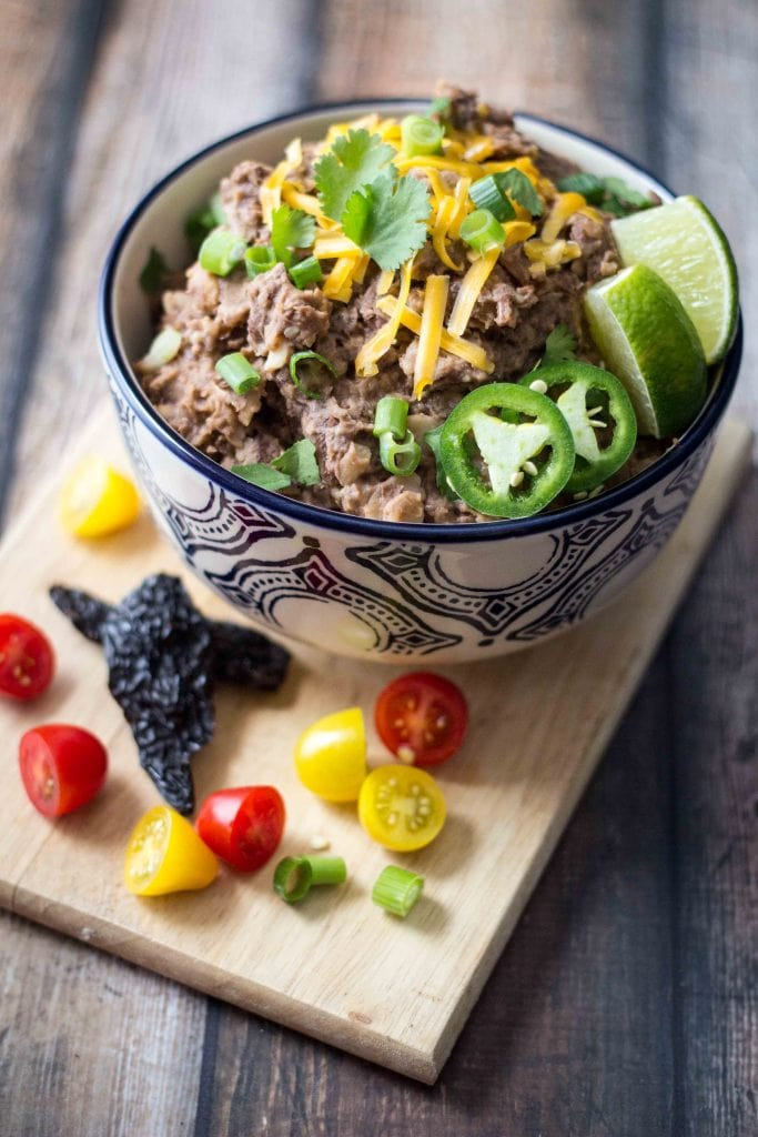 This Vegetarian Smoky Chipotle Refried Beans recipe is a great way to spice up your refried beans for a delicious side dish for your next Mexican dinner!