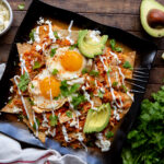 This delicious Mexican Chilaquiles Rojos recipe has triangles of corn tortillas simmered in salsa, and served with cheese, shredded chicken, eggs or beans.