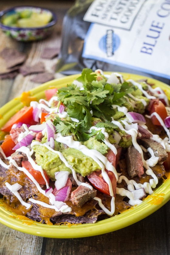 Looking for a carne asada nacho recipe? Here is a great one! This Carne Asada Nachos recipe tops blue corn tortilla chips with cheddar cheese, chopped carne asada, tomatoes, red onion, guacamole, sour cream and cilantro for an amazing nachos taste.