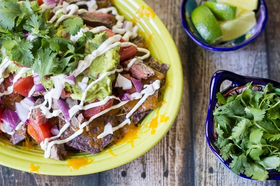 This Best Carne Asada Nachos recipe tops blue corn tortilla chips with cheddar cheese, chopped carne asada, tomatoes, red onion, guacamole, sour cream and cilantro for an amazing nachos taste.