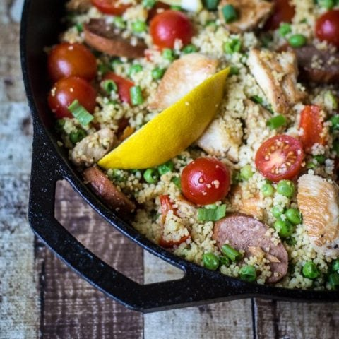 This Couscous Paella recipe blends chicken, sausage and couscous with peas, cherry tomatoes, red bell pepper, garlic, olive oil and spices for a delicious, easy and filling one pan dish!