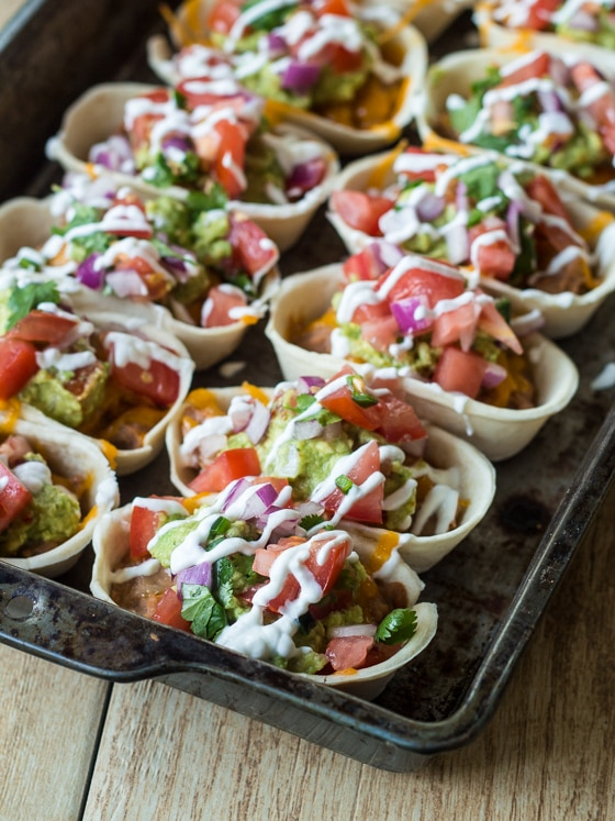 Get all of that layered bean dip flavor with much less work in these two-bite snacks. Like miniature bean burritos, these bean dip bites are topped with melty cheese, seasoned guacamole, fresh pico de gallo, and tangy sour cream. Finger food never tasted so good! These quick and easy Loaded Bean Dip Bites are the perfect snack for after school or while watching the big game.