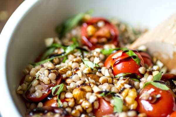 """Whether you call it """"pearl couscous"""" or """"Israeli couscous,"""" there's everything to love about these little balls of pasta. In this recipe, chilled couscous is coated in a simple olive oil dressing, then tossed with tomatoes, basil, and almonds before being finished with a generous drizzle of balsamic glaze. Healthy and delicious!"""
