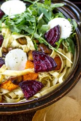 Roasted vegetables, tangy goat cheese, peppery arugula, and nutty almonds transform plain fettuccine noodles into a dinner worth craving!