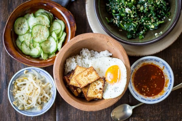 Pan-fried tofu is my protein of choice for Korean Bibimbap Bowls. Topped with seasoned vegetables, a dippy fried egg, and flavorful gochujang sauce, you don't have to be a vegetarian to enjoy this recipe!