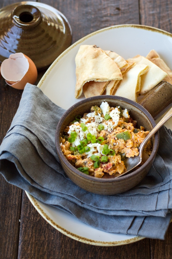 This Menemen recipe (aka Turkish scrambled eggs recipe) combines eggs, onion, bell pepper, tomatoes, feta cheese, garlic and spices to smear over toasted pita chips for a hearty breakfast or an easy weeknight dinner.
