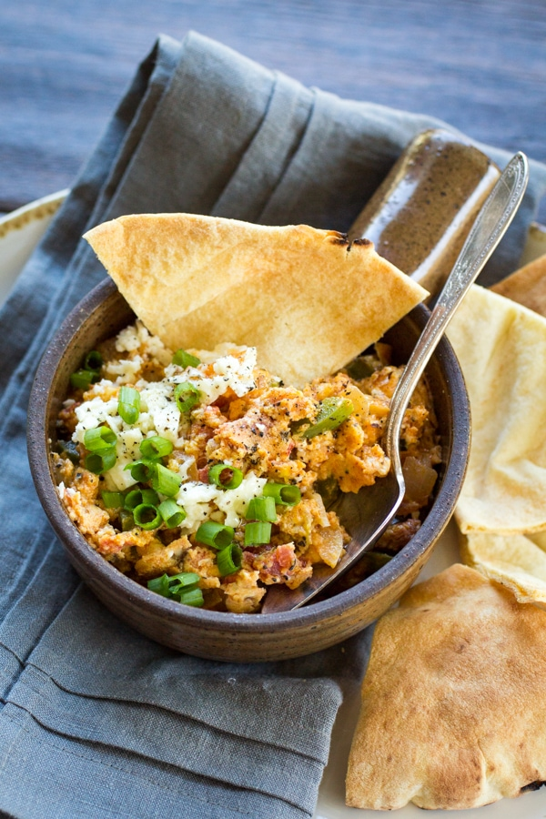 Menemen is just the thing for a hearty breakfast or an easy weeknight dinner. These Turkish scrambled eggs are cooked over low-heat until just set, then smeared over toasted pita chips to make a luscious and richly-spiced meal!