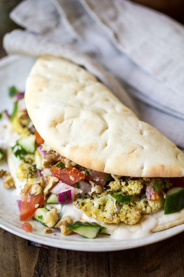 Vegan Pita Sandwiches: made with these vegan pita bread fillings: zaatar roasted cauliflower, Jerusalem salad, and an easy tahini sauce. The perfect vegan lunch!