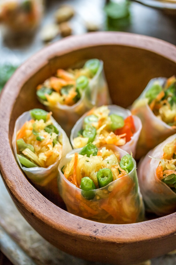 This Thai Style Papaya Salad Rolls recipe wraps up green beans, carrots, tomatoes, green papaya and peanuts with a peanut sauce for a delicious appetizer when you can't decide between fresh rolls and papaya salad!