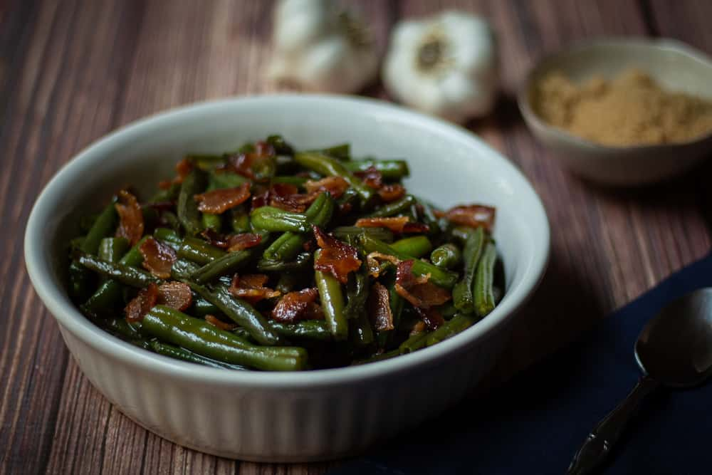 This Bacon and Brown Sugar Arkansas Green Beans recipe uses soy sauce and garlic in its sweet, buttery glaze, coating the green beans to create a delectable side dish.