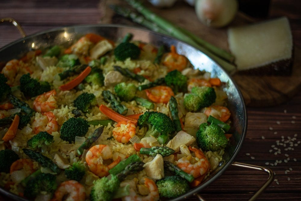 This delicious Shrimp and Chicken Paella is made with broccoli, carrots, and asparagus; then it is topped with the creamy, nutty flavor of Manchego cheese. This authentic paella recipe is delicious and an easy paella recipe too!