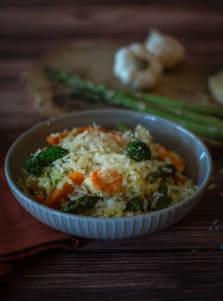 This delicious Shrimp and Chicken Paella is made with broccoli, carrots, and asparagus; then it is topped with the creamy, nutty flavor of Manchego cheese. You might call this chicken and prawn paella recipe, and that is fine. It is a simple paella recipe and delicious!