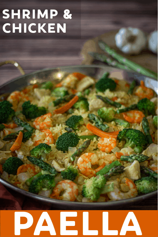 This delicious Shrimp and Chicken Paella is made with broccoli, carrots, and asparagus; then it is topped with the creamy, nutty flavor of Manchego cheese. This is an easy paella recipe you can make at home!
