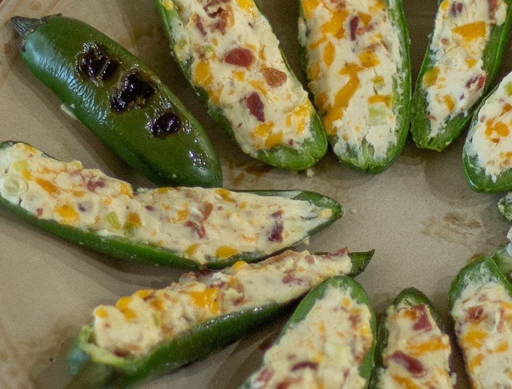 This delicious, Grilled Stuffed Jalapeno recipe will please any crowd with its filling of cream cheese, cheddar cheese, bacon, garlic and green onion and topped with tomatoes, red onions and cilantro.