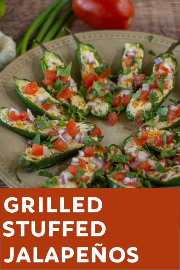 This delicious, Grilled Stuffed Jalapeño recipe will please any crowd with its filling of cream cheese, cheddar cheese, bacon, garlic and green onion and topped with tomatoes, red onions and cilantro.