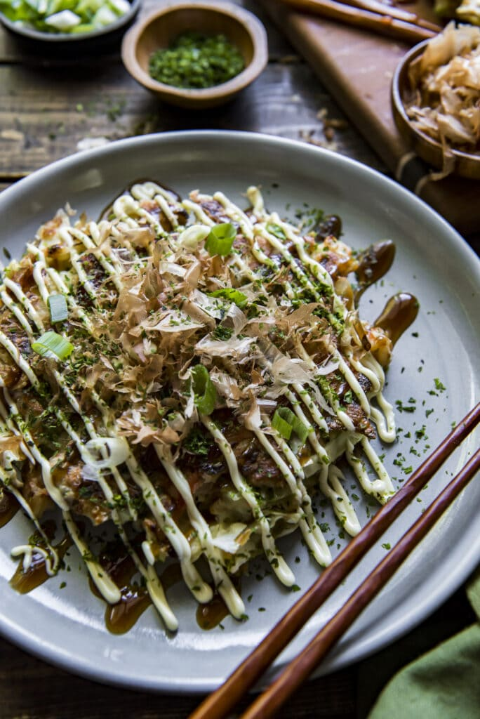 This Easy Okonomiyaki recipe will give you a taste of Japan with this Japanese cabbage pancake that mixes cabbage, ginger, green onions, and shrimp into the batter and then adds bacon and tasty Japanese toppings for an incredible mix of flavors.