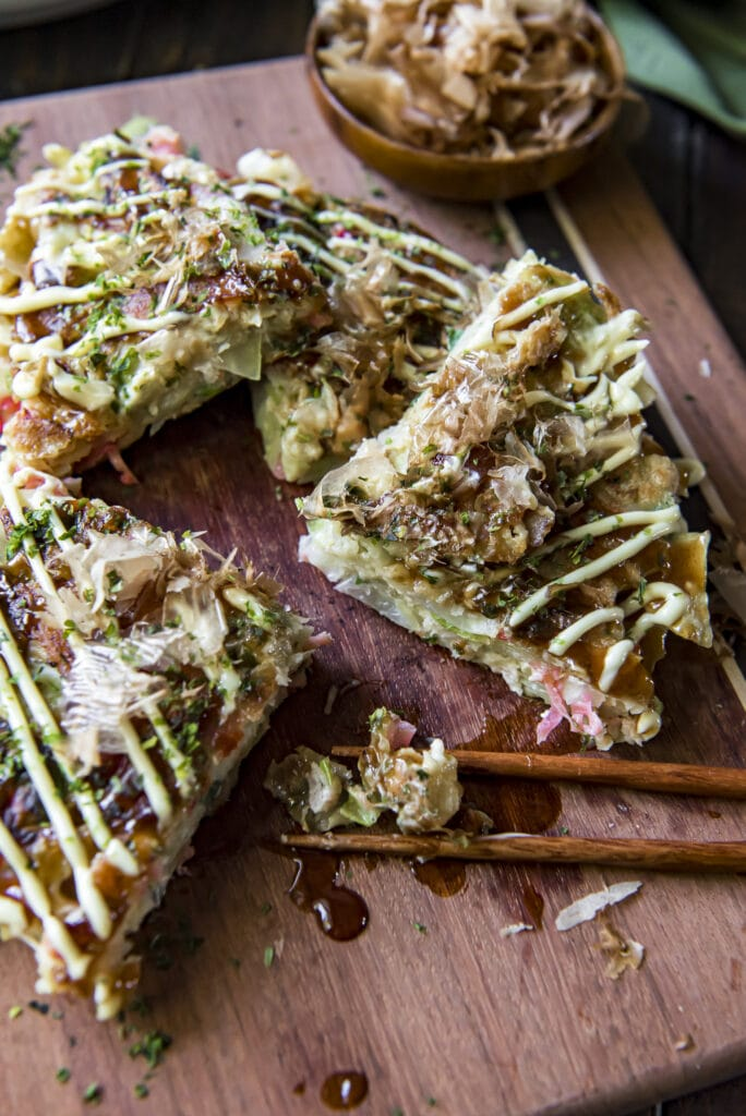 This Japanese Pancake Okonomiyaki recipe mixes cabbage, ginger, green onions, and shrimp into the batter and then adds bacon and tasty Japanese toppings for an incredible mix of flavors.