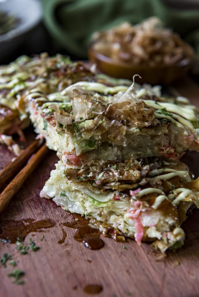 This Easy Japanese Okonomiyaki recipe will give you a taste of Japan with this Japanese savory pancake that mixes cabbage, ginger, green onions, and shrimp into the batter and then adds bacon and tasty Japanese toppings for an incredible mix of flavors.