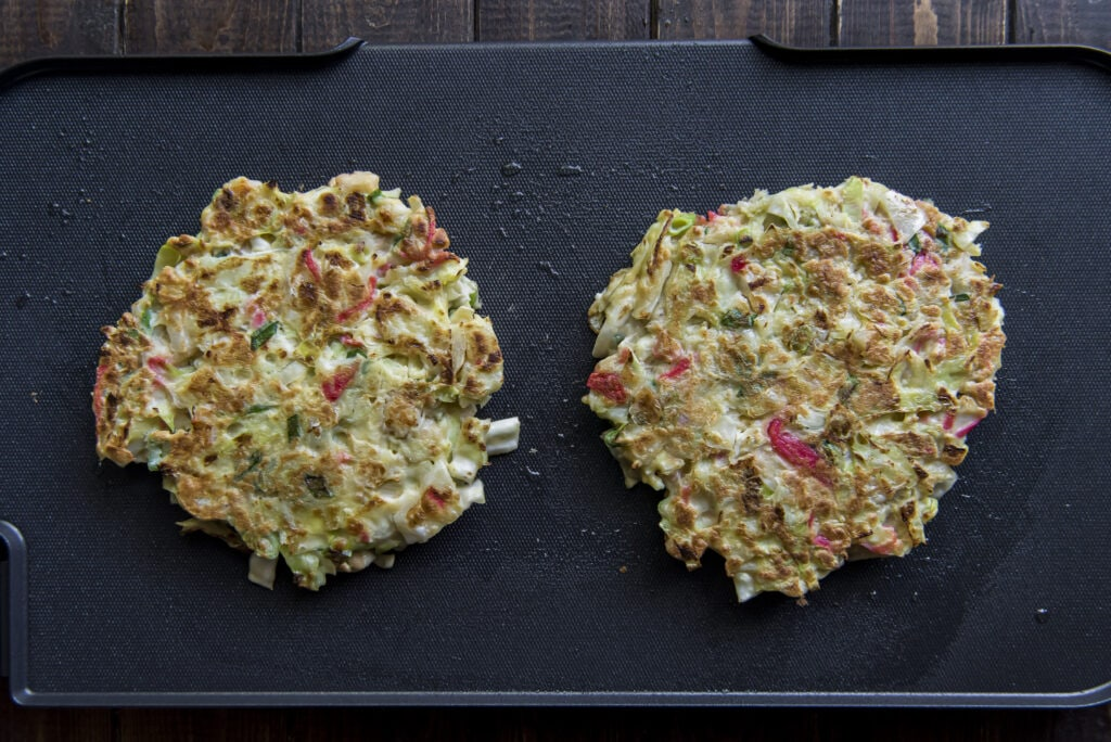 This Easy Okonomiyaki recipe mixes cabbage, ginger, green onions, and shrimp into the batter and then adds bacon and tasty Japanese toppings for an incredible mix of flavors.