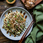 This Easy Okonomiyaki recipe will give you a taste of Japan with this Japanese savory pancake that mixes cabbage, ginger, green onions, and shrimp into the batter and then adds bacon and tasty Japanese toppings for an incredible mix of flavors.