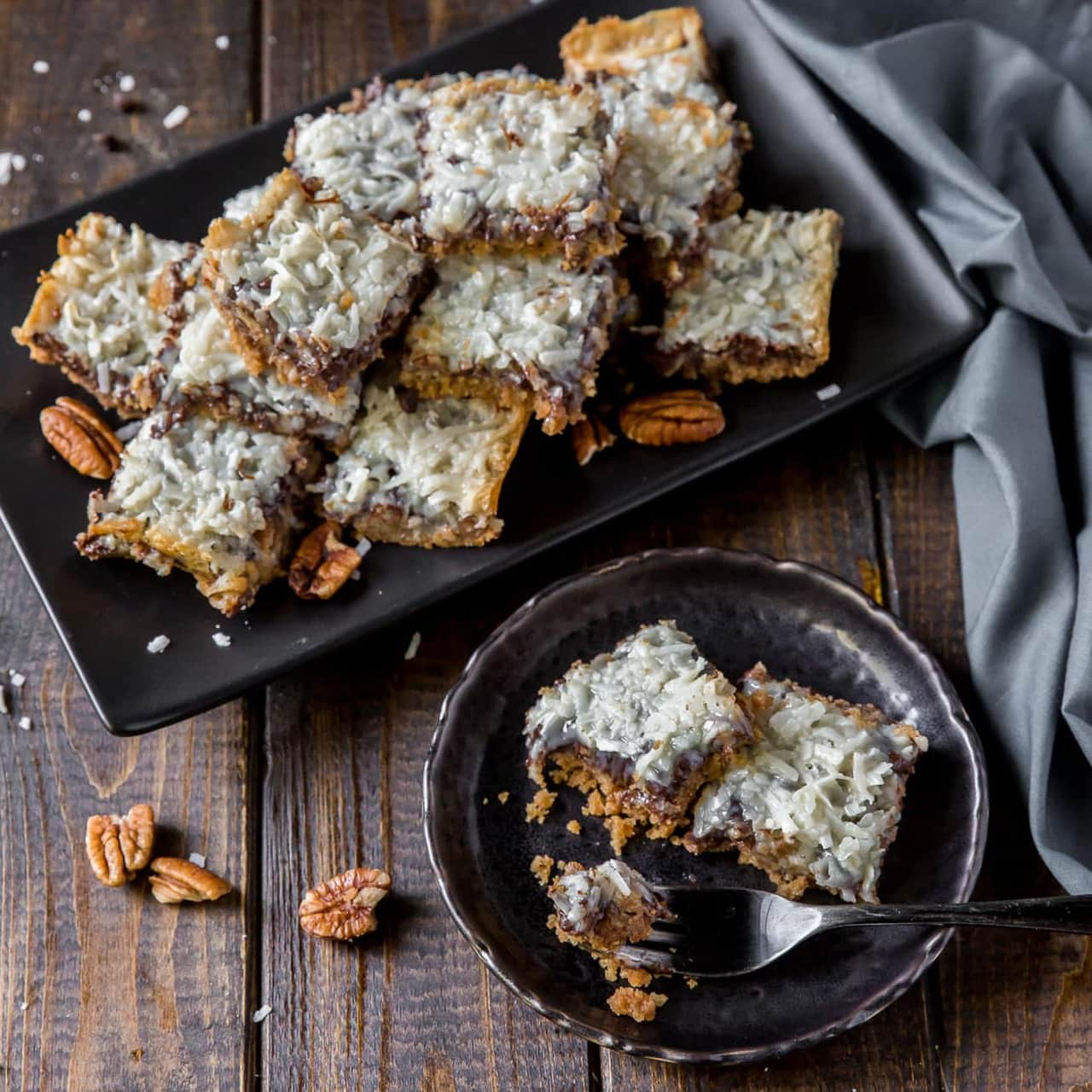 This Hello Dolly Bars recipe (also known as Magic Cookie Bars) is a delicious, family favorite dessert to make and share during the holidays with a buttery graham cracker crust topped with pecans, chocolate chips, coconut and sweetened, condensed milk.
