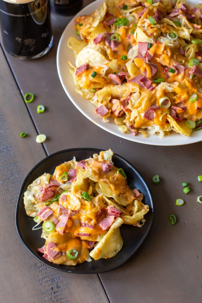 This delicious Irish Nachos with potato chips recipe layered with potato chips, swiss cheese, sauerkraut, corned beef, homemade beer cheese sauce and thousand island dressing will have you river dancing with joy!