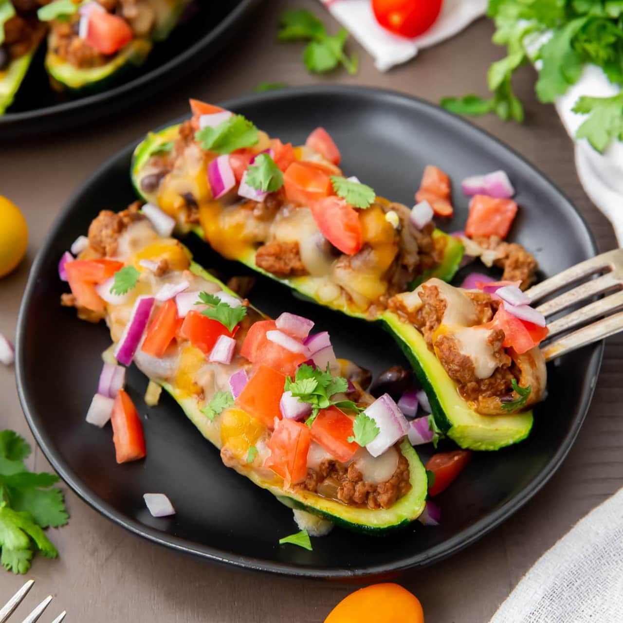 This delicious Taco Zucchini Boats recipe uses fresh zucchini stuffed with taco meat and all your favorite toppings.