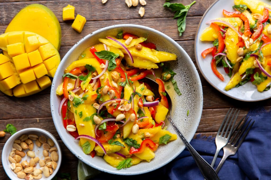 Want a mango salads? Here is one! This Mango Salad recipe has sweet mangoes, crisp bell peppers and onions, and a tangy lime dressing that all pairs together perfectly!