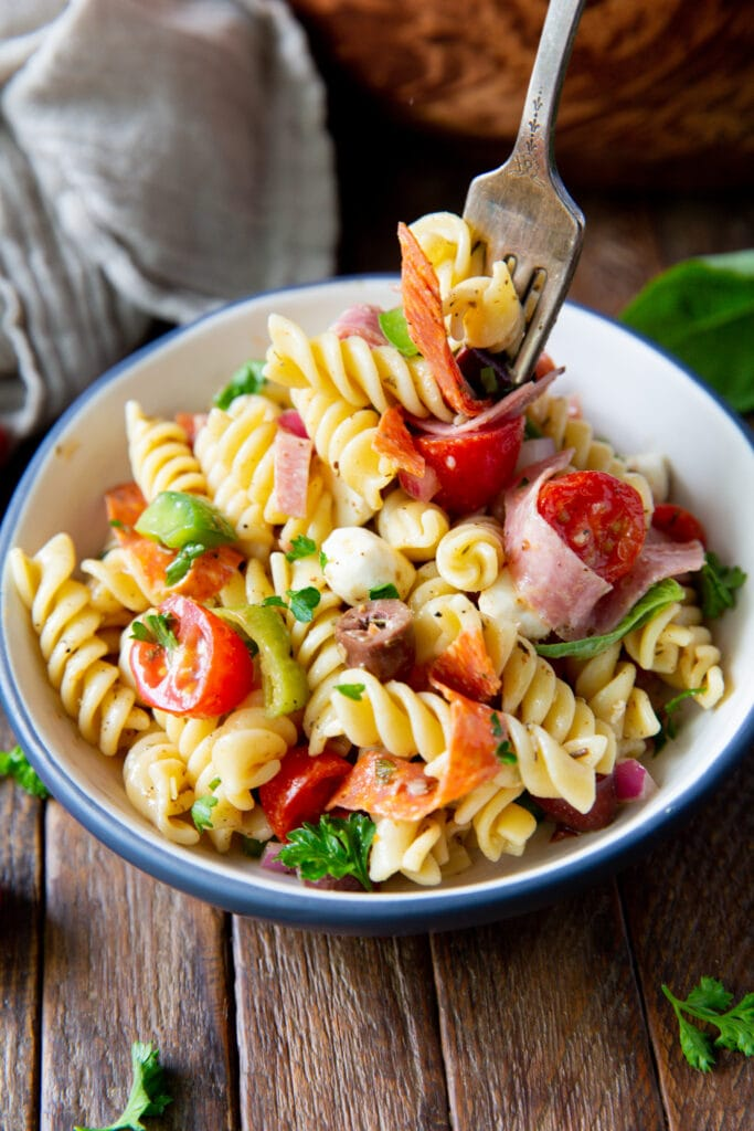 Wanting pasta salad dressing? This Italian Pasta Salad Recipe is a burst of color filled with salami, pepperoncini, Kalamata olives, mozzarella and so much more!