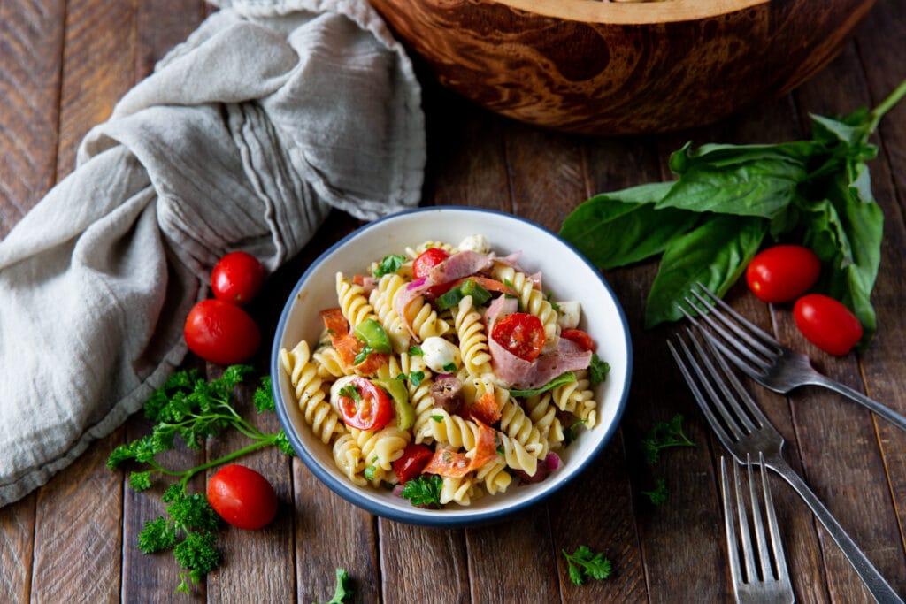 Wanting a recipe for Italian pasta salad? This Italian Pasta Salad Recipe is a burst of color filled with salami, pepperoncini, Kalamata olives, mozzarella and so much more!