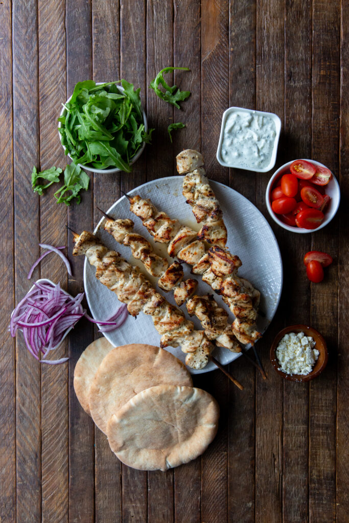 This Chicken Souvlaki Greek recipe is made with a delicious lemon, garlic and spice marinade and so tasty when loaded onto a pita bread with your favorite toppings, like lettuce, tomatoes, onion, tzatziki sauce and feta cheese!