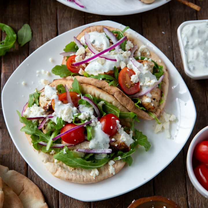 This Greek Chicken Souvlaki recipe is made with a delicious lemon, garlic and spice marinade and so tasty when loaded onto a pita bread with your favorite toppings, like lettuce, tomatoes, onion, tzatziki sauce and feta cheese!